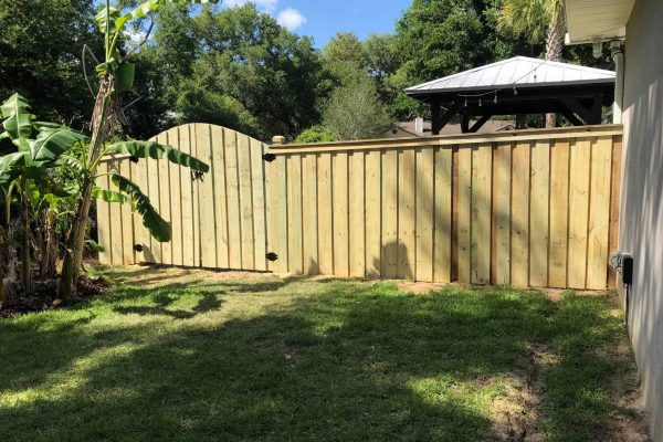 Trimmed And Capped Board On Board Fence With Arched Double Gate